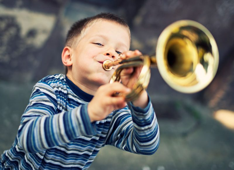 Boy blowing on trumpet